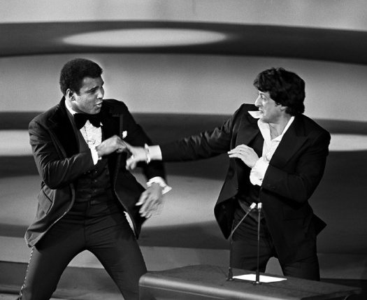 "Muhammad Ali surprised Sylvester Stallone – and the audience at the 49th Academy Awards – when he appeared on stage. The two men briefly engaged in a good-natured spar. Stallone, who was also nominated for acting and writing took home an Oscar as producer of Best Film ""Rocky."""
